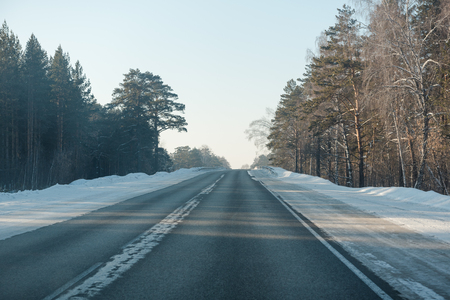 Asphalt road in winter in the forest. Asphalt under the snow. Road in the snow. Winter road. Siberian roads. Stok Fotoğraf - 116783560