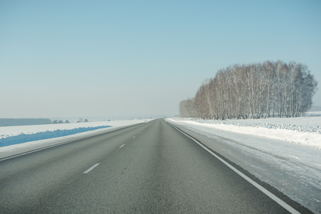 The road in winter. Asphalt road in winter. Road under the snow. Russian roads. Stok Fotoğraf - 116783499