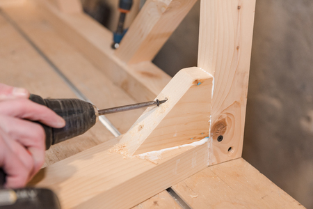 A man is screwing a screw into a wooden table. Carpentry workshop. Work with a screwdriver. Work tool. Stok Fotoğraf