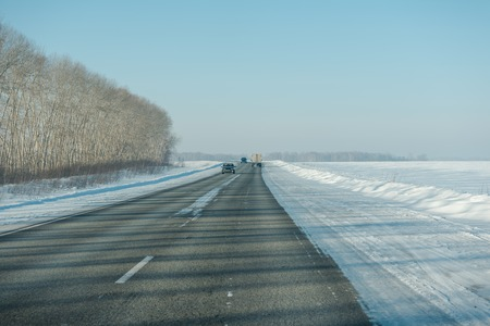 Asphalt road in winter in the forest. Asphalt under the snow. Road in the snow. Winter road. Siberian roads. Stok Fotoğraf - 116783364