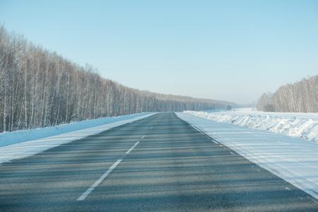 Asphalt road in winter in the forest. Asphalt under the snow. Road in the snow. Winter road. Siberian roads.