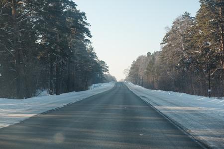Asphalt road in winter in the forest. Asphalt under the snow. Road in the snow. Winter road. Siberian roads. Stok Fotoğraf - 116783447