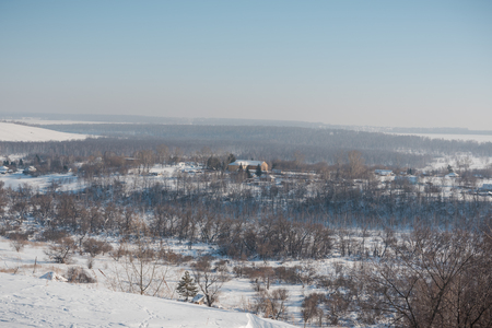 Winter view of the village from above. Houses in the snow. Countryside under the snow. Village in Siberia in the winter.