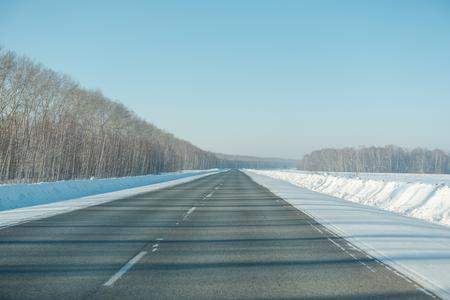 Asphalt road in winter in the forest. Asphalt under the snow. Road in the snow. Winter road. Siberian roads. Stok Fotoğraf - 116783306