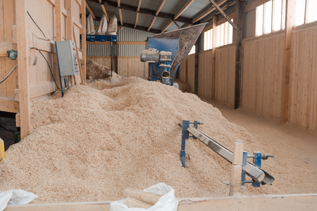 Production of fuel briquettes. Briquettes from sawdust. Pressed chips in briquettes. Sawdust for fuel Stok Fotoğraf - 116783332