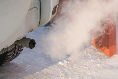 The car smokes in the winter. Smoke from a car pipe. The car is buzzing in the cold. The car is buzzing in the winter outside. Stok Fotoğraf - 116783263