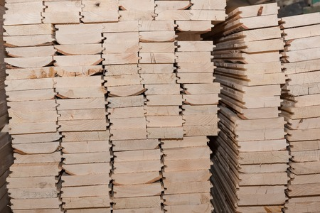 Lumber butts. Boards clad in piles. Euro race, blockhouse, timber emitation. A lot of lumber.