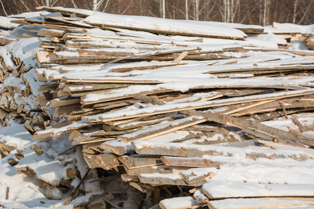 Firewood in a stack. Waste from sawing trees. Waste sawmill. A lot of wooden waste. Departure. Foto de archivo
