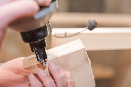 A man squeezes the glue on the wooden part. Carpentry workshop. Professional tool. Do it yourself. Glue for wooden parts. Strongly glue.