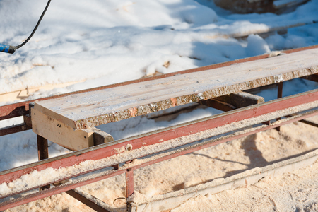 Sawing boards on the sawmill. Cook lumber in winter. Work on the sawmill. Sawing boards in winter.