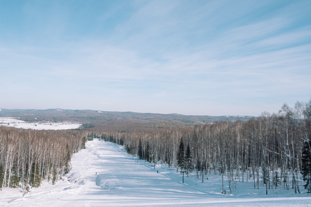 Winter mountain view from above. View down from the mountain in winter. Winter landscape. Winter in Siberia. Trees grow down below.