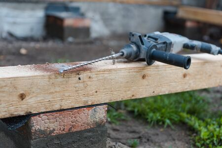 drill a hole in the board. Drill a hole in the timber. drill for wood.