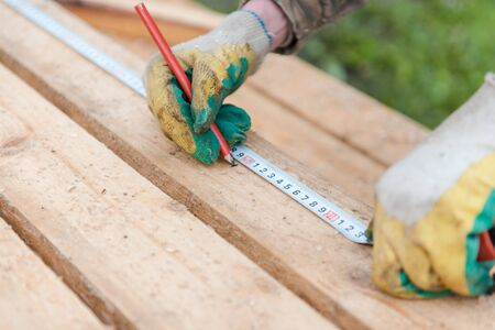 Measure with a ruler on the tree. Measure the distance with a ruler. Measure on the board. Centimeter on the tree. Construction works. Build a house Reklamní fotografie