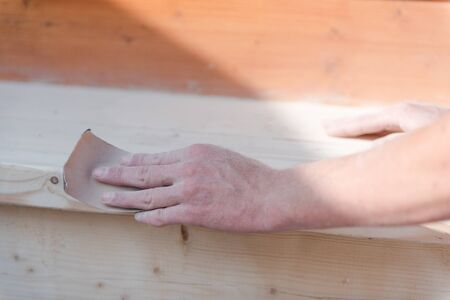 Sand the wood with sandpaper. A man polishes a tree. Work with sandpaper. To make wooden products. Make boards smooth. Joiners works.