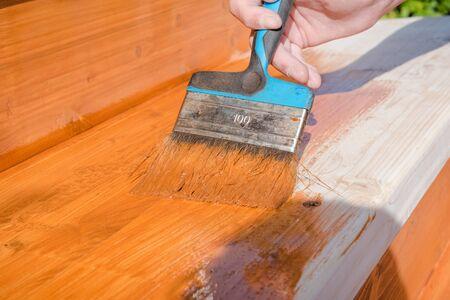 Streichen Sie die Veranda mit oranger Farbe. Dekorieren Sie die Terrasse. Malen Sie die Bretter mit einem breiten Pinsel. Um Reparaturen vorzunehmen. Ein Mann arbeitet mit einer Bürste. Standard-Bild