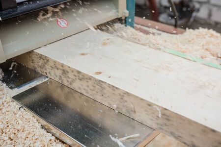 planing boards on a thicknesser. wood shavings. machine for planing wood. carpentry work. joiner's machine. wood processing. Reklamní fotografie
