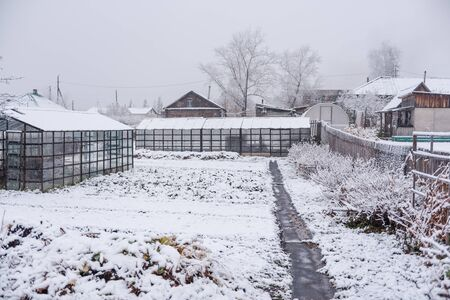 Greenhouses under the snow. Snow. Garden in the snow. Winter season of the year. Cold weather