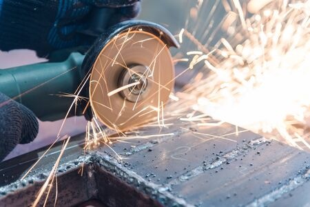 Cut metal with a Angular grinding machine. Sparks are flying. Construction tool grinder. A man is cutting metal. Wear gloves for safety. Use a dangerous tool in work Archivio Fotografico - 135699099