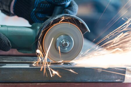 Cut metal with a Angular grinding machine. Sparks are flying. Construction tool grinder. A man is cutting metal. Wear gloves for safety. Use a dangerous tool in work Archivio Fotografico - 135699101