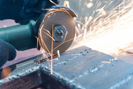 Cut metal with a Angular grinding machine. Sparks are flying. Construction tool grinder. A man is cutting metal. Wear gloves for safety. Use a dangerous tool in work Archivio Fotografico - 135699122