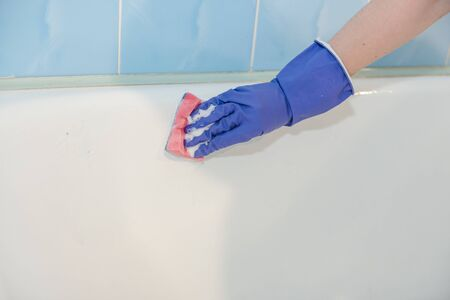 The girl cleans the bath, the water in the shower, clean the bath, the girl cleans the white bath, with rubber gloves, clean up the house Archivio Fotografico - 135699129
