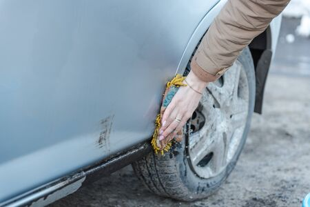 A girl washes a car. To wash the car with a sponge. Foam by car. Clean car. Squeeze a sponge with foam