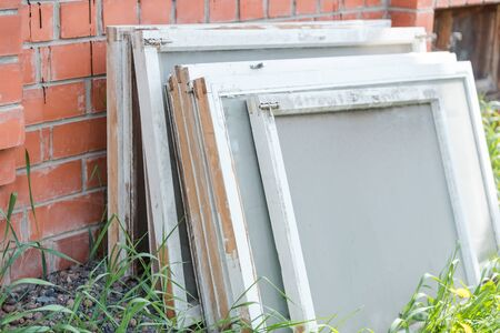 Old window frames. Window frames are on the street. Glass windows. Carry out repairs at home. Windows in the village. Wooden window frames. Glazing