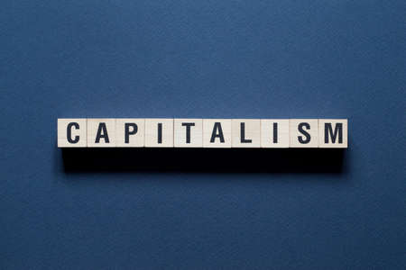 Capitalism Word Written In Wooden Cube.