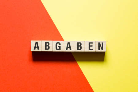 Abgaben word levy in german concept on cubes.