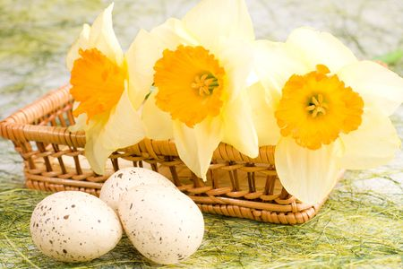 Decorated speckled easter eggs with a bunch of daffodils in the woven basket photo
