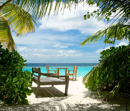 Free table for two and wooden sun bed on the tropical beach   photo