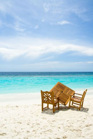 Wooden table and chairs on the sandy beach with ocean view photo