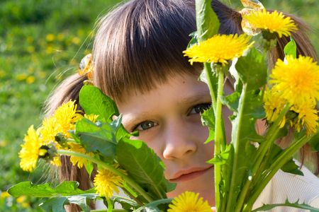 Little girl on the spring meadow peeps out through bunch of dandelions Stock Photo - 4760506