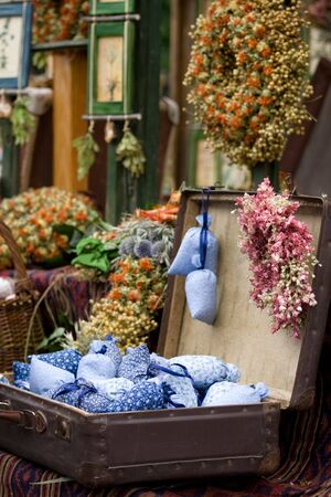 Dried wild flowers and cotton bags with lavender in old fashioned suitcase photo