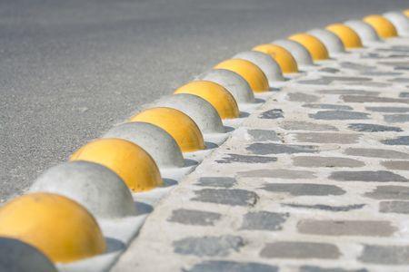 kerb: Bent curb close-up separated asphalt road and cobblestone