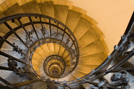 winding up: Spiral staircase, forged handrail and stone steps in old tower Stock Photo