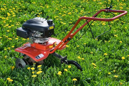 Hand tractor plough from back side on the flowering dandelion field Horizontal photo
