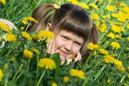 Little cool smiling girl is lying on the flowering dandelion meadow  Stock Photo
