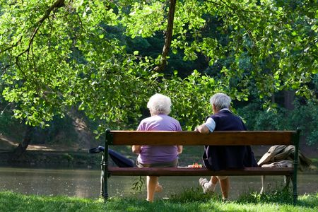 Aged couple enjoy spring morning on the bench near lake in the park  photo