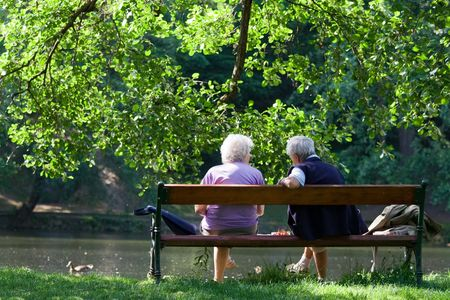 Grandparents are sitting on the bench and talking to each other in the spring park photo
