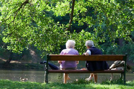 banc de parc: Les grands-parents sont assis sur le banc et de parler les uns aux autres dans le parc au printemps