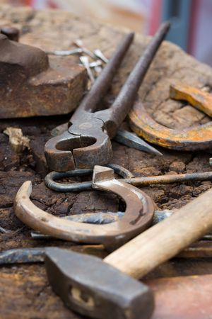 ancient blacksmith: Horseshoes, nippers, hammer and other blacksmith tools close-up