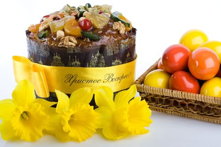Traditional in Eastern Europe Easter cheesecake dessert paskha, colored eggs into the woven basket, and daffodils on the white background photo