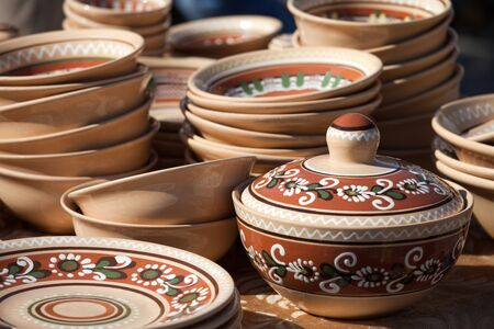 Rustic handmade ceramic pot and clay brown pottery decorated by traditional ornament and pattern at the handicraft market photo