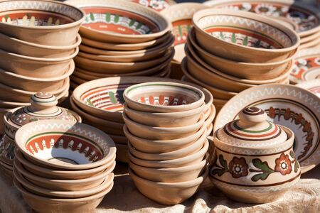 Stack of rustic handmade ceramic brown plates and pots decorated by traditional ornament and pattern at the handicraft market photo