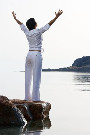 back lighting: Young dressed white woman with raised arms meets sunrise staying barefoot on the sea stone. Back lighting