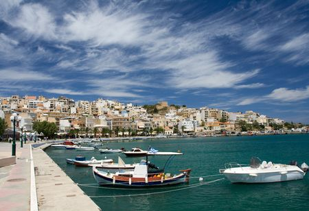 Sea bay with moored boats, promenade in Mediterranean town Sitia Greece Crete and dramatic cirrus clouds in the blue sky
