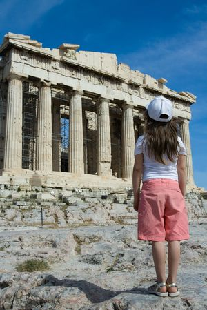 Child in front of Facade of ancient temple Parthenon in Acropolis Athens Greece on the blue sky background Stock Photo