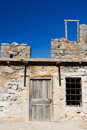 padlocked: Picturesque old Mediterranean style abandoned lopsided rustic stone house with padlocked wooden door and window lattice on blue sky background