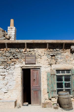 lopsided: Picturesque old Mediterranean style abandoned lopsided rustic stone coffee house with opened wooden sun blind, chimney,  doorway, wine barrel and bench on the blue sky background Stock Photo